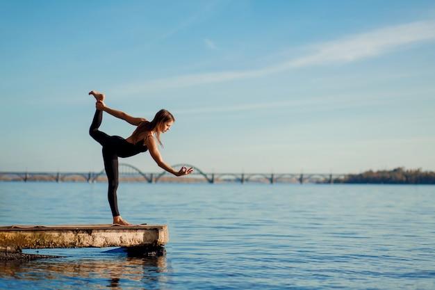 Młoda kobieta ćwiczy jogę ćwiczy przy spokojnym drewnianym molem z miastem. sport i rekreacja w ruchu miejskim Premium Zdjęcia