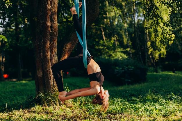 Młoda kobieta ćwiczy komarnicy joga przy drzewem Premium Zdjęcia