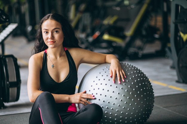 Młoda kobieta ćwiczy z wyposażeniem przy gym Darmowe Zdjęcia