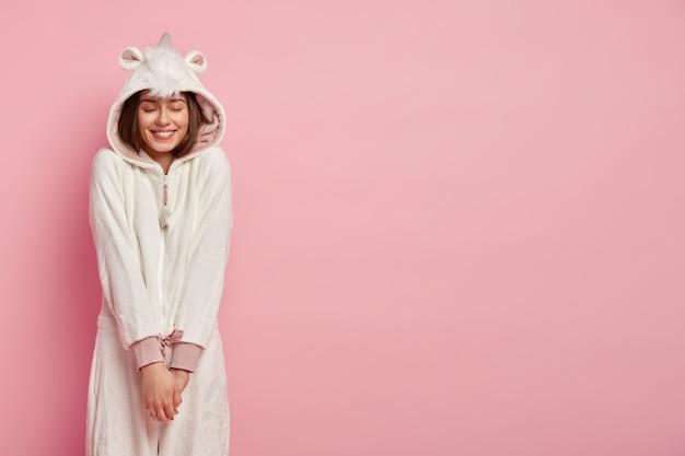 Młoda Kobieta Czuje Przyjemność, Cieszy Się Wygodą W Miękkim Stroju Kigurumi, Trzyma Ręce Razem Darmowe Zdjęcia