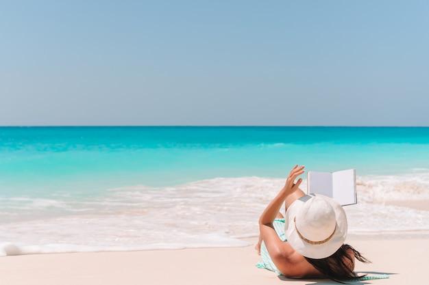 Młoda kobieta, czytanie książki na szezlong na plaży Premium Zdjęcia