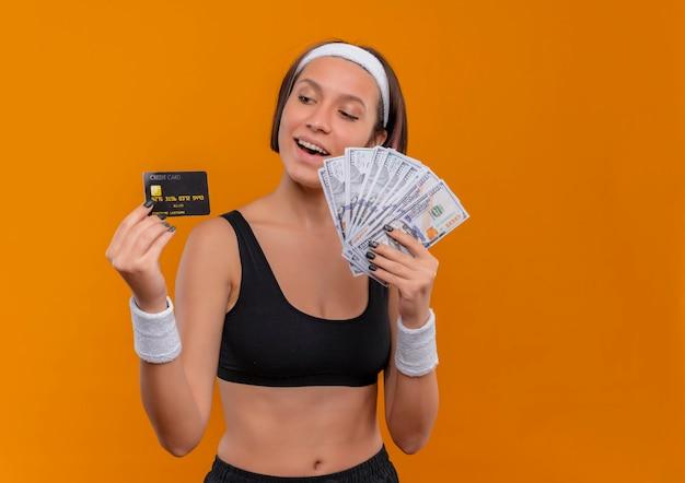 Młoda Kobieta Fitness W Odzieży Sportowej Z Pałąkiem Na Głowę Trzyma Kartę Kredytową I Pokazuje Gotówki, Uśmiechając Się Radośnie Stojąc Na Pomarańczowej ścianie Darmowe Zdjęcia