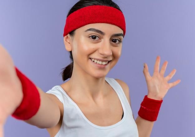 Młoda Kobieta Fitness W Odzieży Sportowej Z Pałąkiem Na Głowę, Uśmiechając Się Wesoło, Czyniąc Powitalny Gest Rękami Stojącymi Na Fioletowej ścianie Darmowe Zdjęcia
