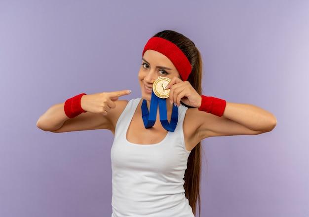 Młoda Kobieta Fitness W Odzieży Sportowej Z Pałąkiem Na Głowę Ze Złotym Medalem Na Szyi, Pokazując I Wskazując Palcem Na To Uśmiechnięty Stojący Nad Szarą ścianą Darmowe Zdjęcia
