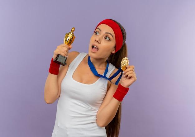 Młoda Kobieta Fitness W Odzieży Sportowej Z Pałąkiem Na Głowę Ze Złotym Medalem Na Szyi, Trzymając Trofeum Patrząc Zdziwiony Darmowe Zdjęcia