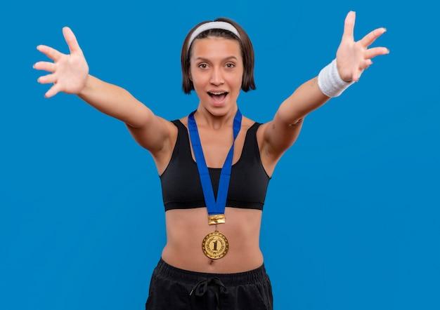 Młoda Kobieta Fitness W Odzieży Sportowej Ze Złotym Medalem Na Szyi, Czyniąc Powitalny Gest Szeroko Otwierając Ręce Stojąc Na Niebieskiej ścianie Darmowe Zdjęcia