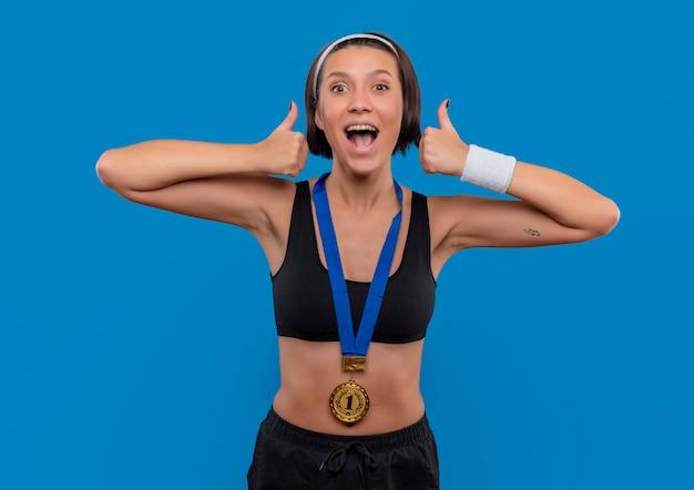 Młoda Kobieta Fitness W Odzieży Sportowej Ze Złotym Medalem Na Szyi, Pokazująca Kciuki Do Góry, Ciesząca Się Swoim Sukcesem Szczęśliwa I Podekscytowana Stojąca Nad Niebieską ścianą Darmowe Zdjęcia