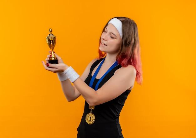 Młoda Kobieta Fitness W Odzieży Sportowej Ze Złotym Medalem Na Szyi Trzymając Trofeum Patrząc Na To Uśmiechnięty Wesoło Stojąc Nad Pomarańczową ścianą Darmowe Zdjęcia