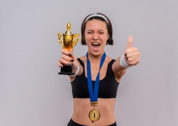 Młoda Kobieta Fitness W Odzieży Sportowej Ze Złotym Medalem Na Szyi, Trzymając Trofeum Szczęśliwa I Podekscytowana, Ciesząc Się Z Jej Sukcesu, Pokazując Kciuki Do Góry Stojąc Nad Białą ścianą Darmowe Zdjęcia