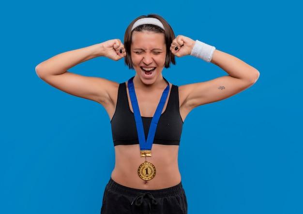 Młoda Kobieta Fitness W Odzieży Sportowej Ze Złotym Medalem Na Szyi Zaciskając Pięści, Ciesząc Się Ze Swojego Sukcesu Stojącego Nad Niebieską ścianą Darmowe Zdjęcia