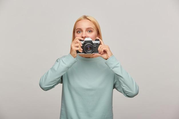 Młoda Kobieta Fotograf Wychodzi Zza Obiektywu, Trzymając Aparat Fotograficzny Retro Vintage Darmowe Zdjęcia