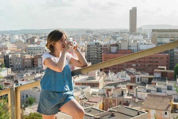 Młoda kobieta fotografuje natychmiastowym aparatem w mieście alicante Premium Zdjęcia