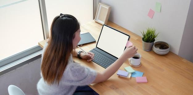 Młoda kobieta freelancer pracuje nad swoim projektem z pustą tabletkę i karteczki Premium Zdjęcia