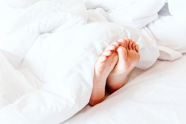 Młoda Kobieta Gołe Stopy Na Białym Kocem Premium Zdjęcia