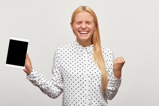 Młoda Kobieta Gotowa Do Skoku Ze Szczęścia, Zaciśnięta Z Radości Pięść, Wygląda Na Uradowaną, Uradowaną Z Tabletką W Dłoni Darmowe Zdjęcia