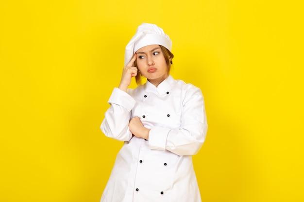 Młoda Kobieta Gotowania W Białym Garniturze Gotować I Białą Czapkę Myślenia Wyrażenie Darmowe Zdjęcia
