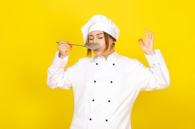 Młoda Kobieta Gotowania W Białym Garniturze Kucharza I Białej Czapce Stwarzających Myślenie Trzymając Srebrną łyżkę Degustację Darmowe Zdjęcia