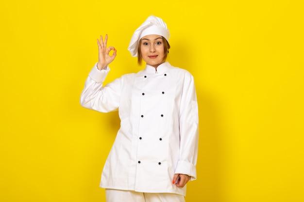 Młoda Kobieta Gotowania W Białym Garniturze Kucharza I Białej Czapce Uśmiecha Się Dobrze Znak Darmowe Zdjęcia