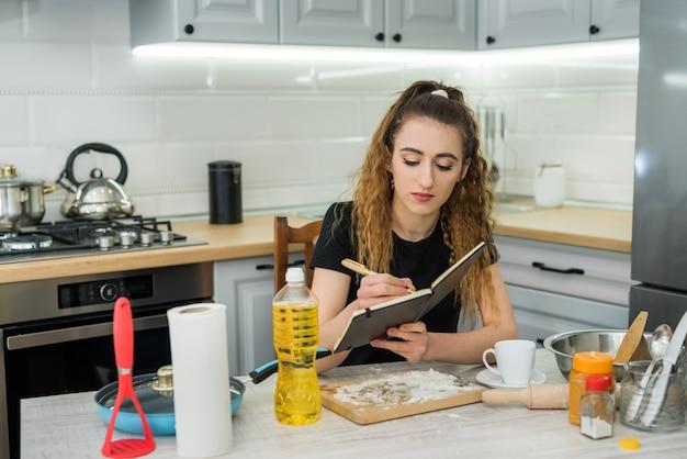 Młoda Kobieta Gotuje Ciasto Z Mąki, Czytając Przepis Notatnika W Kuchennym Stole. Zdrowe Jedzenie Premium Zdjęcia