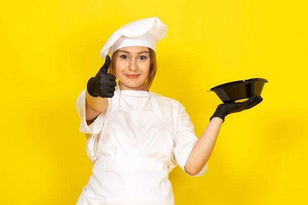 Młoda Kobieta Gotuje W Białym Garniturze I Białej Czapce W Czarne Rękawiczki Przedstawiające Czarną Miskę Darmowe Zdjęcia