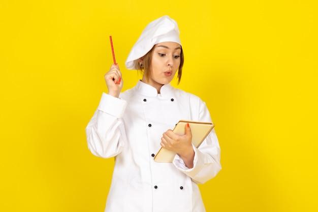 Młoda Kobieta Gotuje W Białym Garniturze I Białej Czapce, Zapisując Notatki Darmowe Zdjęcia