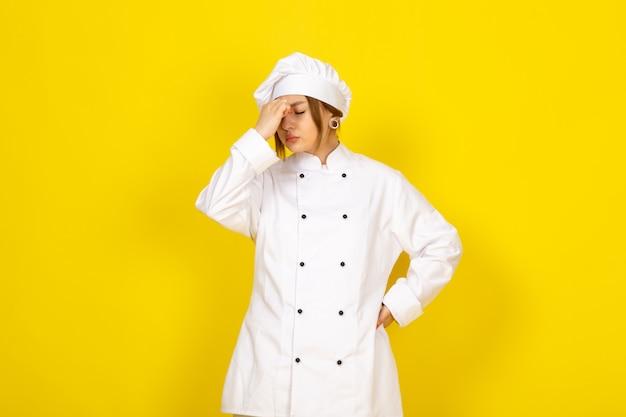 Młoda Kobieta Gotuje W Białym Garniturze I Białej Czapce Zmęczona, Odczuwając Silny Ból Głowy Darmowe Zdjęcia