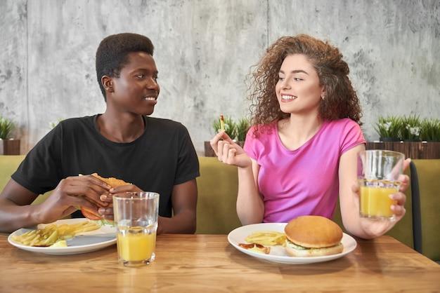 Młoda Kobieta I Mężczyzna Jedzenie Hamburgerów, Frytki W Kawiarni. Premium Zdjęcia