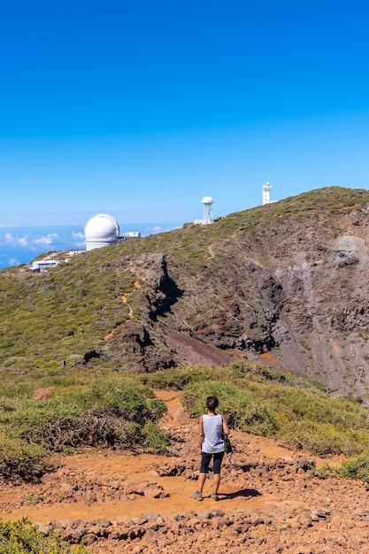 Młoda Kobieta Idąca Obok Teleskopów Parku Narodowego Roque De Los Muchachos Na Szczycie Caldera De Taburiente, La Palma, Wyspy Kanaryjskie. Hiszpania Premium Zdjęcia