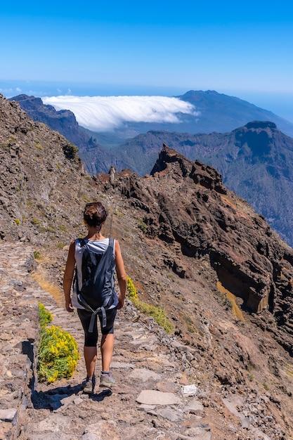 Młoda Kobieta Idąca ścieżką Roque De Los Muchachos Na Szczycie Caldera De Taburiente, La Palma, Wyspy Kanaryjskie. Hiszpania Premium Zdjęcia