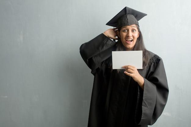 Młoda Kobieta Indonezyjskie Ukończył Na ścianie Zaskoczony I Zszokowany, Patrząc Z Szeroko Otwartymi Oczami Premium Zdjęcia