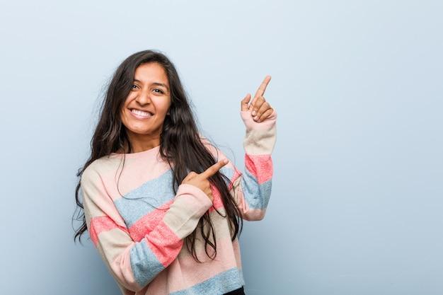 Młoda kobieta indyjska wskazując palcami wskazującymi na przestrzeń kopii, wyrażając podniecenie i pragnienie. Premium Zdjęcia