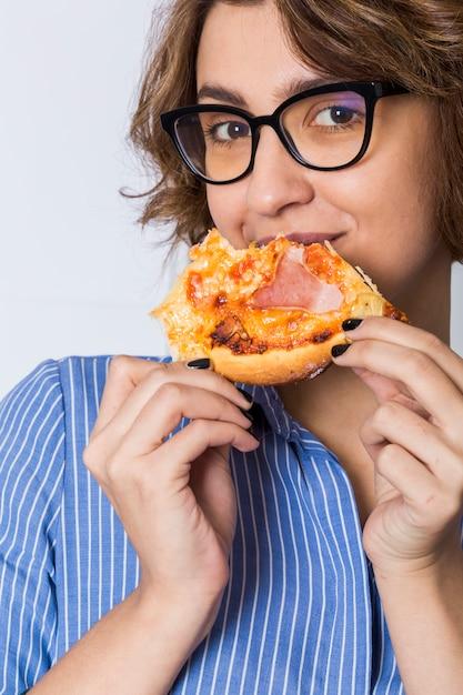 Młoda kobieta je pizzę odizolowywającą na białym tle patrzeje kamera Darmowe Zdjęcia