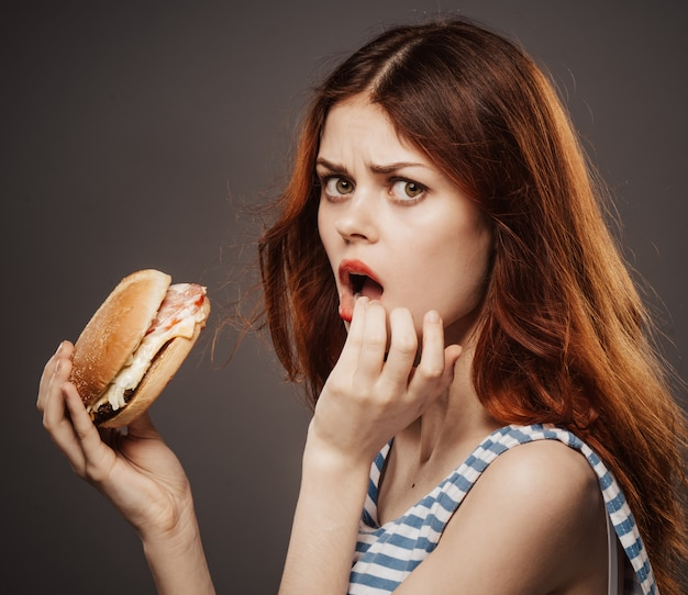 Młoda Kobieta Je Soczystego Hamburger, Wyśmienicie Fasta Food Hamburger W Studiu Premium Zdjęcia