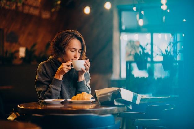 Młoda Kobieta Jedzenie Rogaliki W Kawiarni Darmowe Zdjęcia