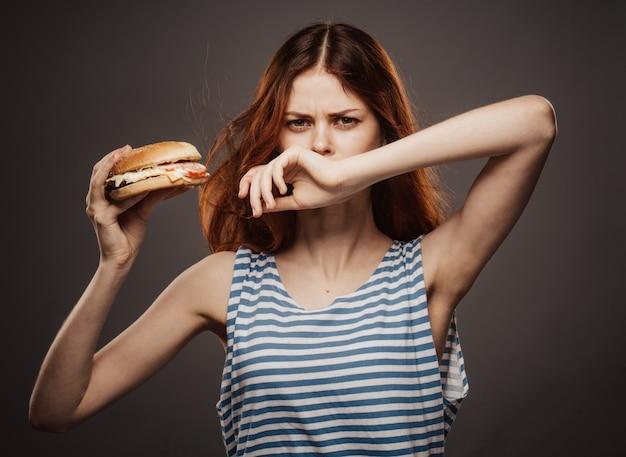 Młoda Kobieta Jedzenie Soczystego Hamburgera, Pyszne Hamburgery Fast Food Premium Zdjęcia