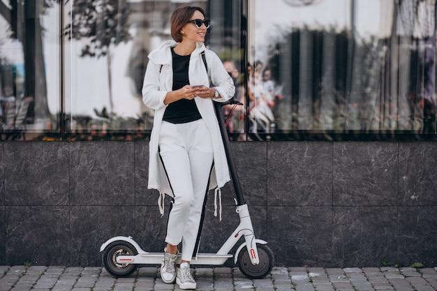 Młoda kobieta jedzie scotter w miasteczku i używa telefon Darmowe Zdjęcia
