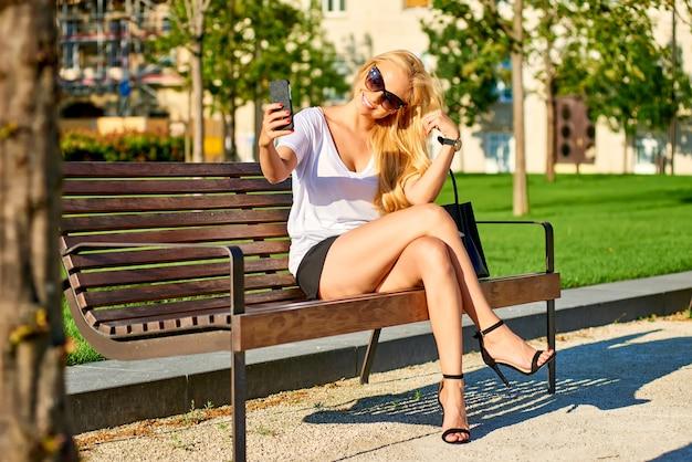 Młoda Kobieta Jest Usytuowanym Na ławce I Bierze Selfie Premium Zdjęcia