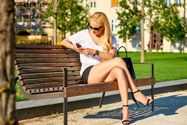 Młoda Kobieta Jest Usytuowanym Na ławce I Używa Jej Telefon Premium Zdjęcia