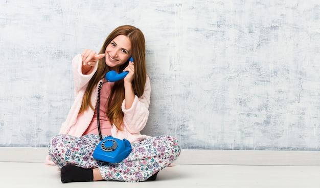 Młoda Kobieta Kaukaski Gospodarstwa Wesoły Uśmiech Na Telefon Stacjonarny, Wskazując Na Przód. Premium Zdjęcia