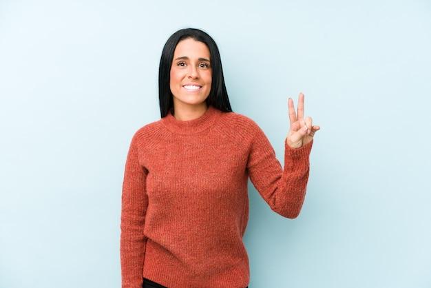 Młoda Kobieta Kaukaski Na Białym Tle Na Niebieskiej ścianie Pokazując Znak Zwycięstwa I Szeroko Uśmiechając Się. Premium Zdjęcia
