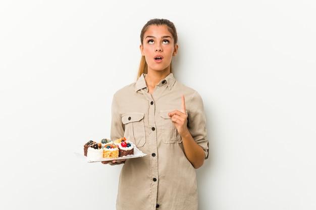 Młoda Kobieta Kaukaski Trzymając Słodkie Ciasta Wskazując Do Góry Z Otwartymi Ustami. Premium Zdjęcia
