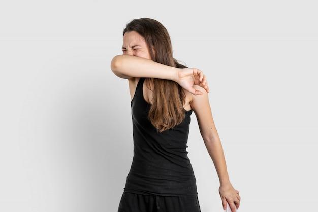Młoda Kobieta Kicha Do łokcia. Zapalenie Płuc Lub Choroba Wirusowa. Pandemia Covida-19 Premium Zdjęcia