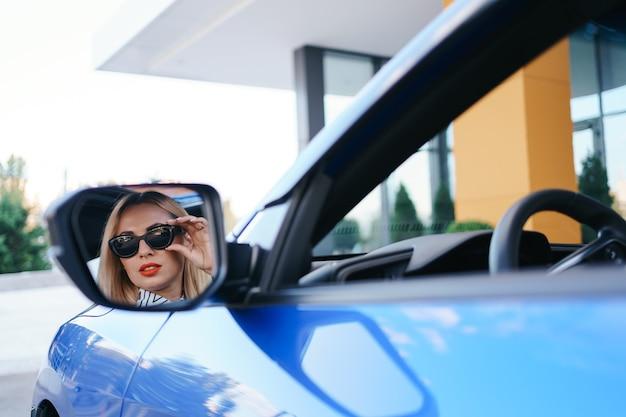Młoda Kobieta Kierowca Patrząc W Lusterko Boczne Samochodu, Upewniając Się, że Linia Jest Wolna Przed Wykonaniem Skrętu. Darmowe Zdjęcia