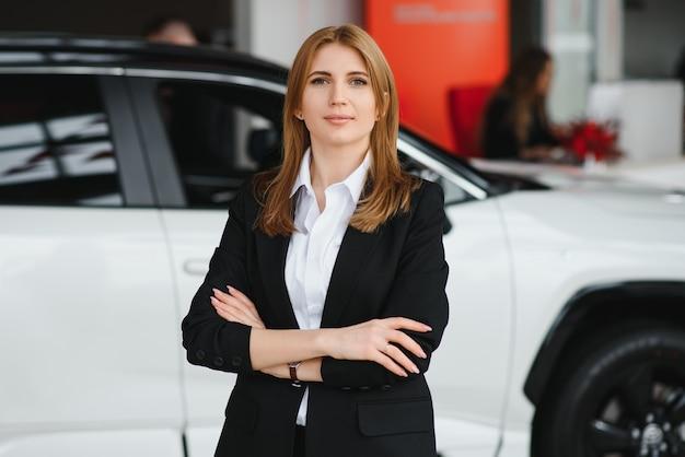 Młoda Kobieta Konsultant W Salonie Stojącym W Pobliżu Samochodu Premium Zdjęcia