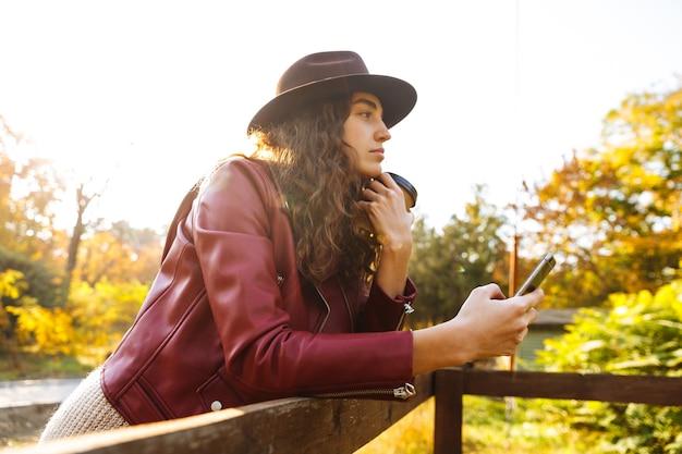 Młoda Kobieta Kręcone Spaceru W Parku Jesienią Picia Kawy Przy Użyciu Telefonu Komórkowego. Premium Zdjęcia