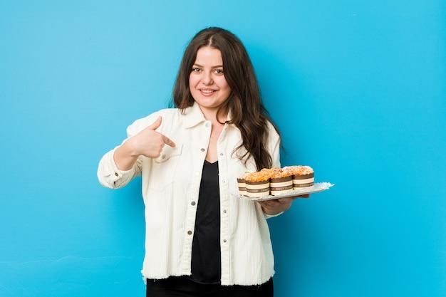 Młoda Kobieta Krzywego Gospodarstwa Osobę Babeczki, Wskazując Się Dumna I Pewna Siebie Premium Zdjęcia