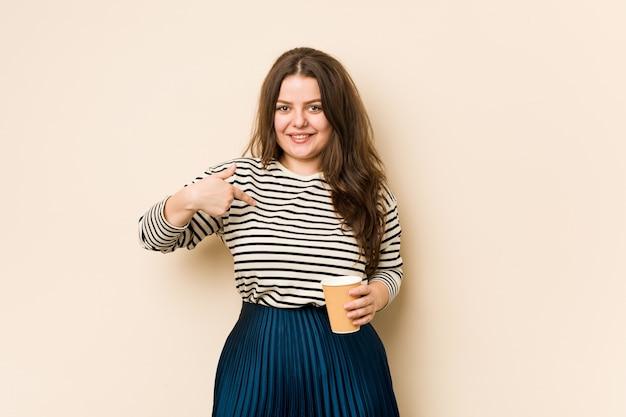 Młoda Kobieta Krzywego Gospodarstwa Osoby Kawy, Wskazując Ręką Na Przestrzeń Kopii Koszuli, Dumna I Pewna Siebie Premium Zdjęcia