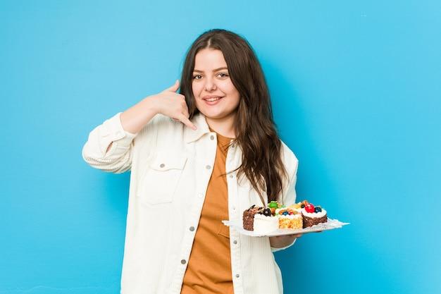 Młoda Kobieta Krzywego Gospodarstwa Słodkie Ciasta Pokazując Telefon Komórkowy Gest Z Palcami. Premium Zdjęcia