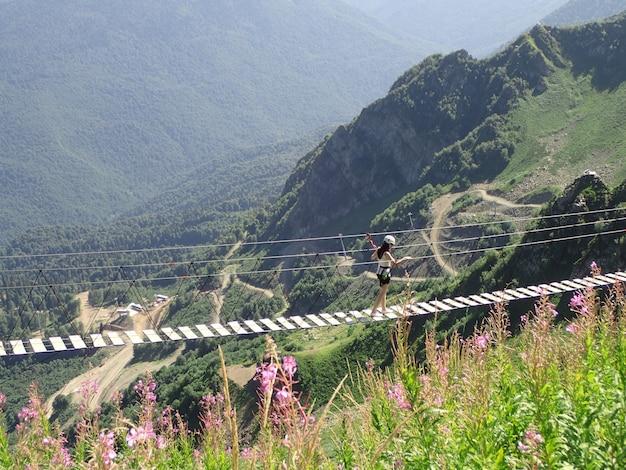 Młoda kobieta krzyżuje otchłań na linowym moscie, sochi, rosja Premium Zdjęcia