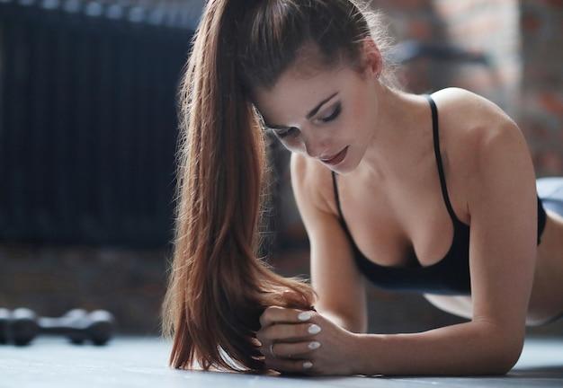 Młoda Kobieta Lekkoatletycznego Robi Jej Rutynowych ćwiczeń W Domu Darmowe Zdjęcia